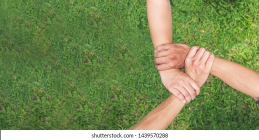 Authentic triangle partners hands together concept. Three hands holding tight promise mission teamwork on green ecosystem business. Customer make triangle three hands of trust to promise unified team