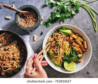 Authentic Vegetarian vegan tofu  Nok Chou padthai noodle with tamarind sauce. Hand holding chopsticks. Crush peanut in rock mortar and pan on the side. Coriandre on loft style grey cement table.
