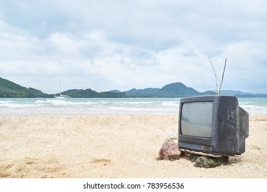 Authentic view of forgotten old fashioned tv standing on beach in front of azure sea. Concept of freedom and innocence, refusal of communication, connection to uninhabited island.