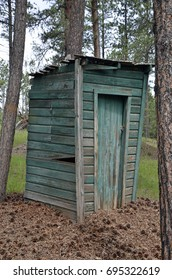 An authentic vintage outhouse with the wood plank sides showing signs of aging, surrounded by pine needles and cones.