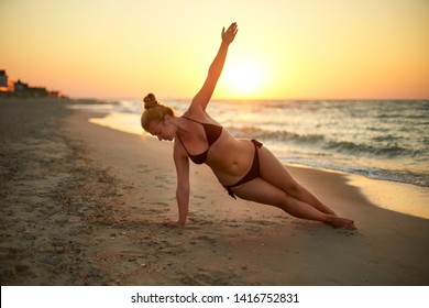 Authentic woman in swimsuit doing yoga vasisthasana on the beach in the morning. Real unretouched shape girl silhouette in side plank asana near sea on sunrise. Body positive female training on sunset