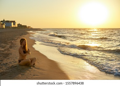 Authentic woman in swimsuit doing yoga padmasana on the beach in the morning. Real unretouched shape girl silhouette in lotus pose asana near sea on sunrise. Body positive female training on sunset.