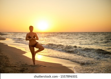 Authentic woman in swimsuit doing yoga vrikshasana on the beach in the morning. Real unretouched shape girl silhouette in tree pose asana near sea on sunrise. Body positive female training on sunset