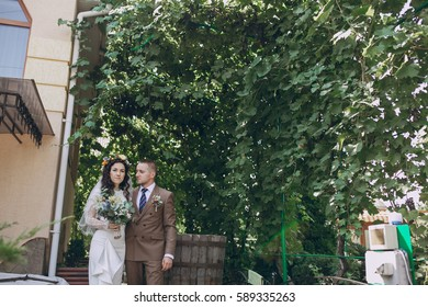 authentic wonderful young couple wedding bride in a wreath of flowers and decorations