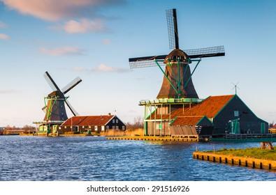 Authentic Zaandam mills on the water channel in Zaanstad village. Zaanse Schans Windmills and famous Netherlands canals, Europe.