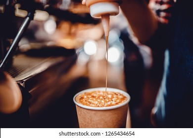 Author coffee, bartender before serving, pours caramel syrup, topping into finished drink in paper cup. Background is blurred