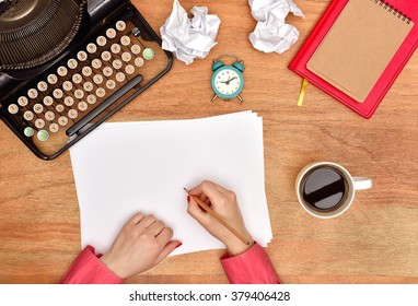 Author hands make notes in a blank page, View from above