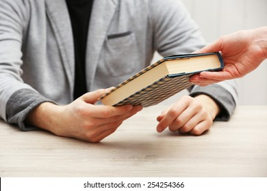 Author signing autograph in own book at wooden table on white planks background
