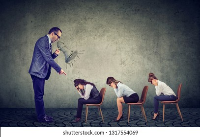 Authoritarian angry boss businessman screaming in megaphone giving orders to sad looking down female employees