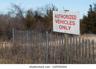 Authorized Vehicles Only sign posted along a wood fence protecting entrance to park trail into the woods on a beautiful winter day
