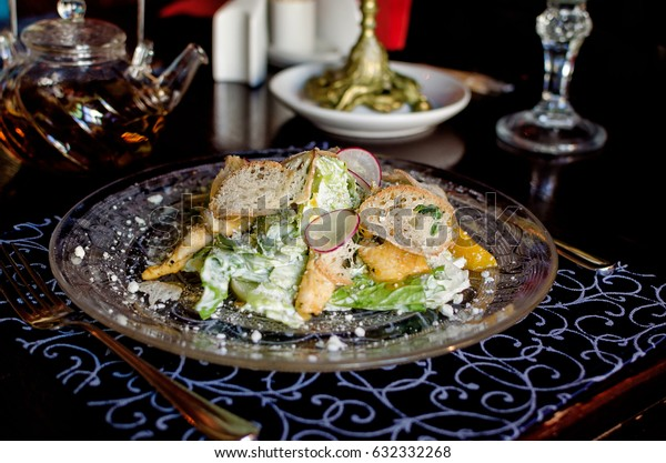 Author's Caesar salad in beautiful vintage dishes on a table in a restaurant