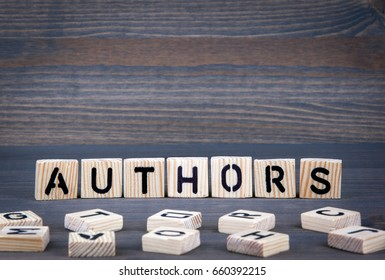 Authors word written on wood block. Dark wood background with texture.