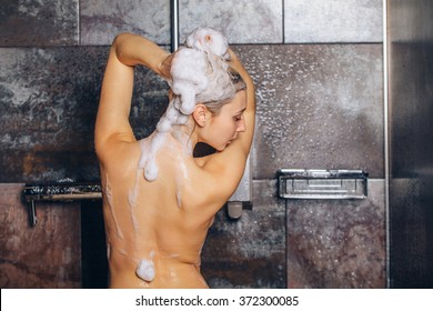 Autiful woman standing at the shower. is washing her hair.