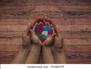 Autism awareness concept with heart of colorful pieces. Woman's and child's hands holding a multicolored heart.