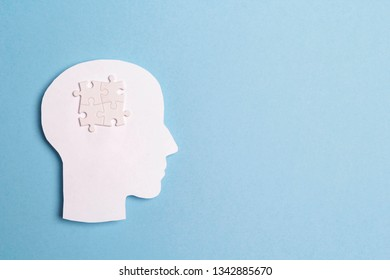 Autism Awareness Day concept with puzzles brain symbol on blue background. Autism Spectrum Disorder (ASD) concept.