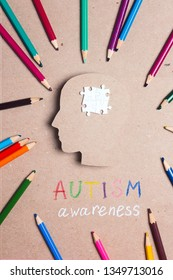 Autism Awareness Day concept with puzzles brain symbol and color pencils. Autism Spectrum Disorder (ASD) concept.