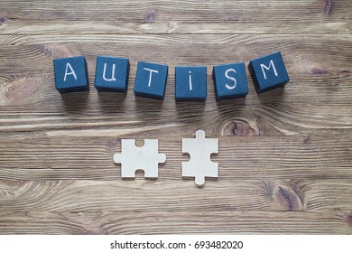 Autism awareness. Autism Spectrum Disorder (ASD). Black wooden cubes with word AUTISM and puzzles on a wooden background, top view, flat lay. Concept of autism word.