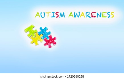 Autism awareness  text. Blue background. Puzzles painted with crayons.