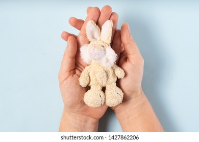 Autism concept with hands holding toy bunny on a blue background. Autism Awareness Day. Autism Spectrum Disorder ASD concept