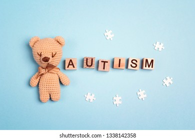 Autism concept with toy bear and word on wooden cubes on a blue background. Autism Awareness Day. Autism Spectrum Disorder (ASD) concept.