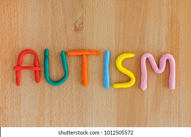 Autism. Autism spectrum disorder. Autism word made out of playdough. Wooden background. Close up.