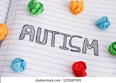 Autism. Autism spectrum disorder. Autism word on notebook sheet with some colorful crumpled paper balls on it. Close up.