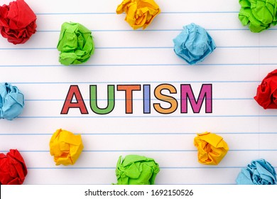 Autism. Autism spectrum disorder. Autism word on notebook sheet with some colorful crumpled paper balls around it. Close up.
