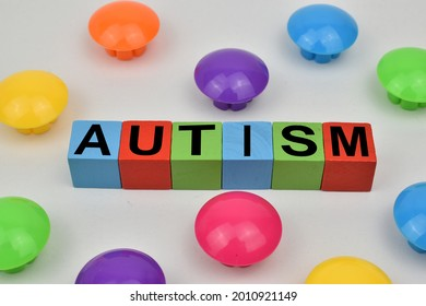 Autism Word Concept On Wooden Cube with colored buttons and white background