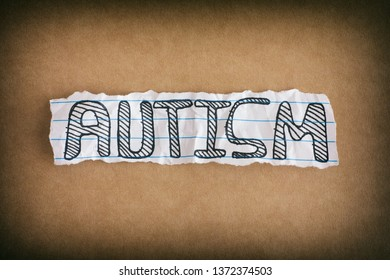 Autism. Word Autism on brown background. Close up.