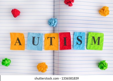 Autism. Word Autism on notebook sheet with some colorful crumpled paper balls around it. Close up.