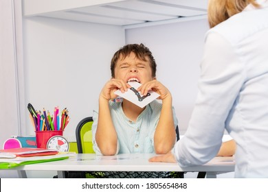 Autistic child bite card expressing negative emotions, throwing tantrums while learning numbers sitting by teacher during ABA therapy