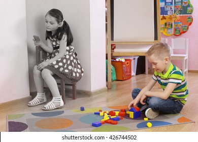 autistic girl. The child sits in the corner. Punished child. Frustrated, thoughtful girl