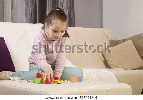 autistic girl concentrating playing with blocks. the girl does not respond to the world around us. immersed in thought