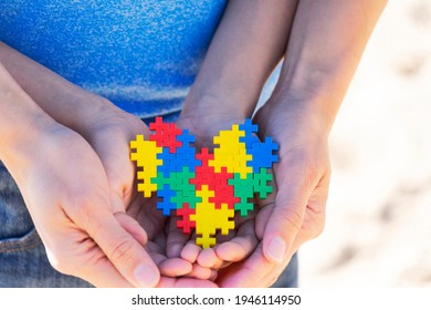 Autistic kid hands supported by mother holding multicolored puzzle heart. World autism awareness day concept.