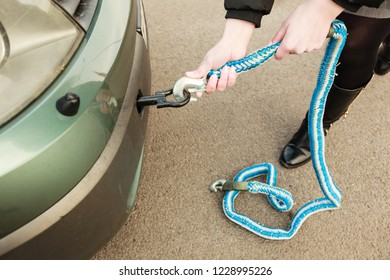 Auto assistance and insurance, troubles while traveling concept. Someone putting tow rope on towbar