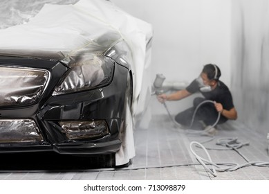 Auto body repair series: Black car being paint in paint booth