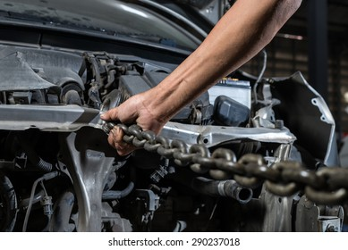 Auto body repair series : Hand of worker adjust hook for auto body pulling