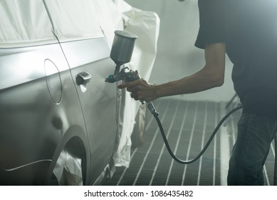 Auto body repair series: Worker painting black car in paint booth