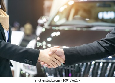 auto business, car sale, deal, gesture and people concept new owner and shaking hands in auto show or salon