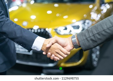 auto business, car sale, deal, gesture and people concept -new owner and shaking hands in auto show or salon