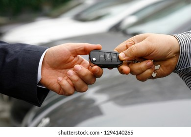auto business, car sale, deal, gesture and people concept - close up of dealer giving key