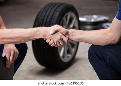 Auto business, car sale, deal, gesture and people concept - close up of men shaking hands with car tire background in car service salon.
