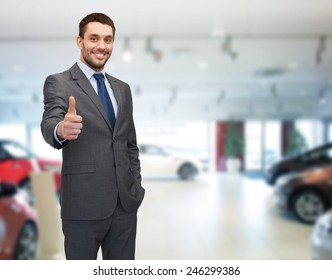 auto business, car sale, gesture and people concept - smiling businessman showing thumbs up over auto show background