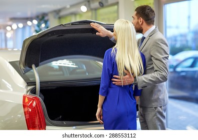 auto business, car sale and people concept - happy couple choosing car in auto show or salon