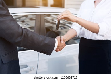 Auto business, car sale. Saleswoman giving key to new owner at car