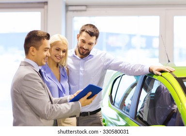 auto business, car sale, technology and people concept - happy couple with car dealer in auto show or salon