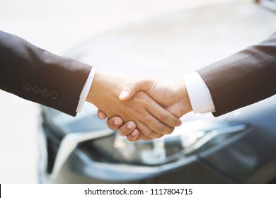 auto business. Close up of a business man dealer offer car to new owner and hand shake between two congratulations to customers. filter tone outdoor sunny in the morning.