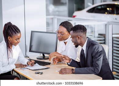 auto business, sale and people concept - happy african couple with dealer buying car in auto showroom or salon
