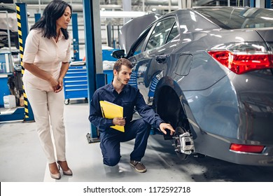 Auto car repair service center. A female customer and mechanic checking car breaks