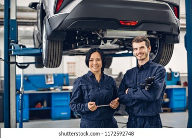 Auto car repair service center. Two happy mechanics - man and woman standing by the car